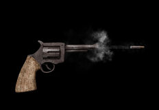 Shooting gun. Side view of an old fashioned gun emitting smoke while shooting a bullet Royalty Free Stock Photography