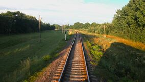 Shooting from high speed train which moving along the railroad in the summer greenery. Railroad travel or railway