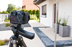 Shooting house exterior, photographer camera, tripod and ballhead. Professional architecture photographer tools: DSLR camera on tripod with modern flexible royalty free stock images