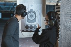 Shooting instructor pointing on used target. In shooting range royalty free stock image