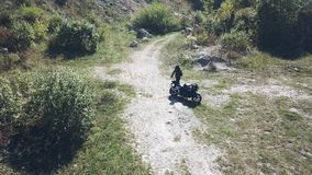 A motorcyclist rides his bike on a dirt road stock video footage
