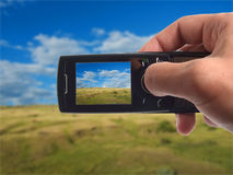 Shooting landscape with mobile phone. Photo on screen and background is my own shot Royalty Free Stock Photo