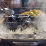 Shooting of large steaming pans, steam in the foreground focused, vegetable pan in the background deliberately blurred. Depth of field stock image