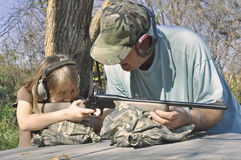Man teaching girl to shoot Stock Image
