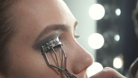 Shooting of master using eyelash curler. Video of visagist using eyelash curler in beauty studio stock video