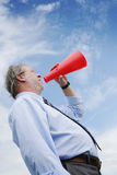 Shooting in a megaphone. Senior business man shooting through a red megaphone Stock Images