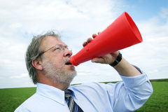Shooting in a megaphone. Senior business man shooting a message through a red megaphone Stock Photo
