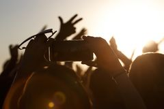 Shooting on a mobile phone during the summer music festival. Black silhouette of raised hands stock photography