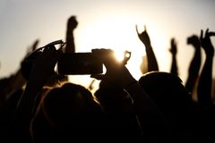 Shooting on a mobile phone during the summer music festival. Black silhouette of raised hands royalty free stock photos