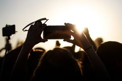 Shooting on a mobile phone during the summer music festival. Black silhouette of raised hands stock photos