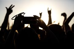 Shooting on a mobile phone during the summer music festival. Black silhouette of raised hands stock photo