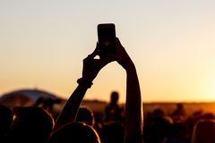 Shooting on a mobile phone during the summer music festival. Black silhouette of raised hands stock images