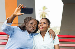 Shooting with a mobile phone. These young women sitting on a bench are photographed with a cell phone Royalty Free Stock Images