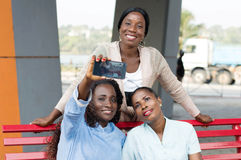Shooting with a mobile phone. These young women sitting on a bench are photographed with a cell phone Royalty Free Stock Image