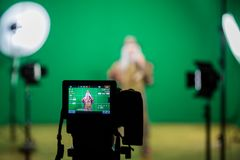 Shooting the movie on a green screen. The chroma key. Studio videography. Actor in theatrical costume. The camera and lighting equipment stock photo