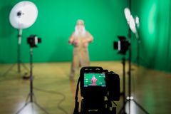 Shooting the movie on a green screen. The chroma key. Studio videography. Actor in theatrical costume. The camera and lighting equipment royalty free stock photo