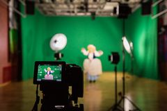 Shooting the movie on a green screen. The chroma key. Studio videography. Actress in theatrical costume. The camera and lighting equipment royalty free stock photos