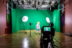 Shooting the movie on a green screen. The chroma key. Studio videography. Actress in theatrical costume. The camera and lighting equipment Royalty Free Stock Photography
