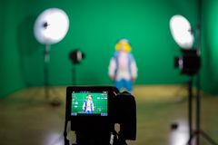 Shooting the movie on a green screen. The chroma key. Studio videography. Actress in theatrical costume. The camera and lighting equipment Royalty Free Stock Images