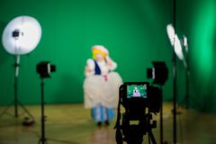 Shooting the movie on a green screen. The chroma key. Studio videography. Actress in theatrical costume. The camera and lighting equipment stock photos