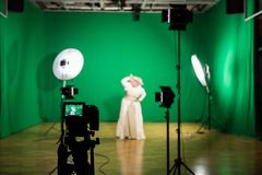 Shooting the movie on a green screen. The chroma key. Studio videography. Actress in theatrical costume. The camera and lighting equipment stock image