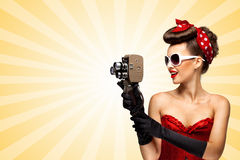 Shooting old movie. Vintage photo of glamorous pinup girl wearing a red sexy corset, filming with an old retro cinema 8 mm camera on colorful abstract cartoon Royalty Free Stock Photography