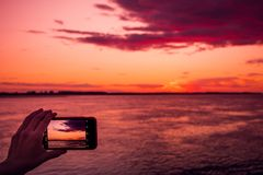 Shooting the sunset on a smartphone stock image