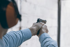 Shooting with a pistol. Man aiming pistol in shooting range. Royalty Free Stock Image