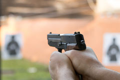 Shooting with a pistol. Man aiming pistol in shooting range. Gun Stock Images