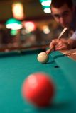 Shooting Pool. A player concentrates to shoot a pool ball royalty free stock photo