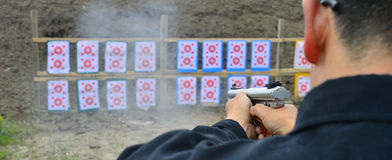 Shooting range. Man aiming at a target and shooting an automatic rifle for Stock Photo