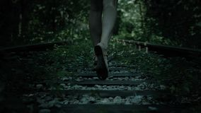 Night view of fleeing legs frightened girl. Railway in forest.
