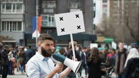 Shooting on a shooter from a megaphone. Many people on background in slow motion. Angry adult young man with a banner in hands go and shouts loudspeaker rally stock video footage