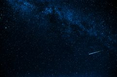 Shooting star in background a starry blue dark sky stock photo