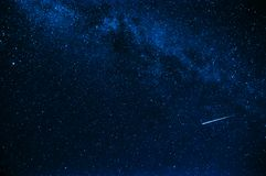 Shooting star in background a starry blue sky royalty free stock photography