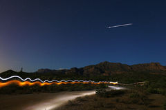 Shooting Star in Night Sky & Light Painting of Runner Stock Image