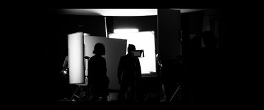 Shooting studio behind the scenes in silhouette images. Which film crew team working for filming movie or video with professional lighting and equipment such as stock photo