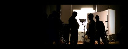 Shooting studio behind the scenes in silhouette images. Which film crew team working for filming movie or video with professional lighting and equipment such as royalty free stock image