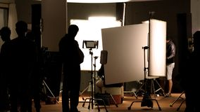Shooting studio behind the scenes in silhouette images. Which film crew team working for filming movie or video with professional lighting and equipment such as stock images