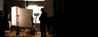 Shooting studio behind the scenes in silhouette images. Which film crew team working for filming movie or video with professional lighting and equipment such as royalty free stock images