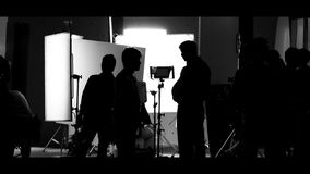 Shooting studio behind the scenes in silhouette images. Which film crew team working for filming movie or video with professional lighting and equipment such as stock image