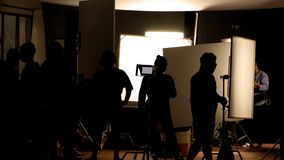 Shooting studio behind the scenes in silhouette images. Which film crew team working for filming movie or video with professional lighting and equipment such as royalty free stock photos