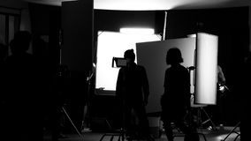 Shooting studio behind the scenes in silhouette images. Which film crew team working for filming movie or video with professional lighting and equipment such as stock photos