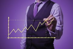 Businessman draws a growth graph. Shooting in the Studio .A businessman in a waistcoat ,shirt and tie on a purple background draws graph Stock Photo