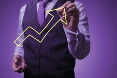 Businessman draws an big growing arrow. Shooting in the Studio .A businessman in a waistcoat ,shirt and tie on a purple background draws growth arrow Royalty Free Stock Photography