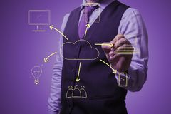 Businessman draws a virtual cloud. Shooting in the Studio .A businessman in a waistcoat ,shirt and tie on a purple background draws virtual cloud appliances Royalty Free Stock Images