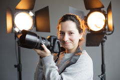 Shooting in the studio, working with light. Girl with a camera in the studio on the background lighting. hipster photographer royalty free stock image
