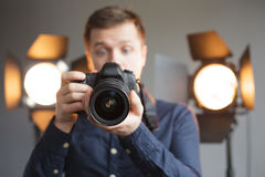 Shooting in the studio, working with light. Man with a camera in the studio on the background lighting looks in screen with surprise stock images