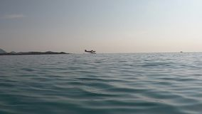 Shooting on the surface of the water on the sea flat in the morning backlight with reflections and a seaplane on the horizon. In. And out of water stock video footage