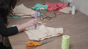 Shooting of tailor gluing pastes on woman`s panties